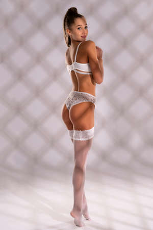 Slender woman in white lingerie in studio