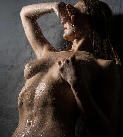 Beautiful woman posing against gray wall