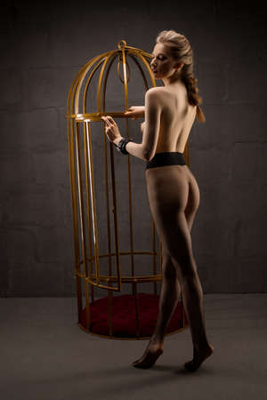 Sexy topless woman standing near bdsm cage 版權商用圖片