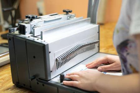 Anonymous woman working on book binding machine