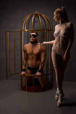 Sexy couple with BDSM accessories in cage Banque d'images