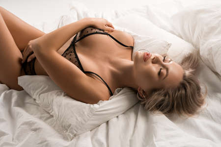 Alluring lady in lingerie lying on bed