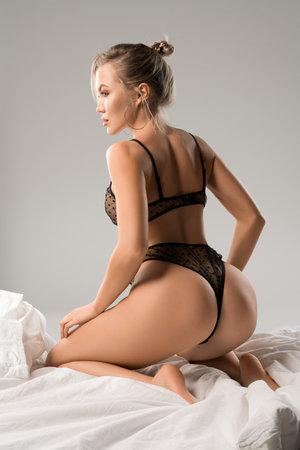 Gorgeous model in black lingerie on studio bed