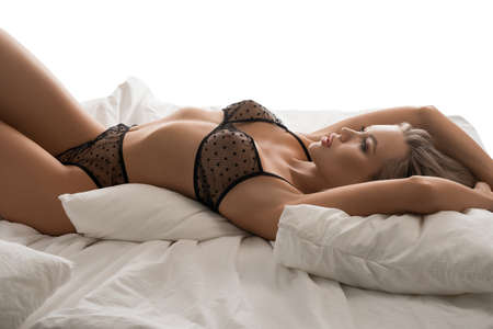 Pretty blond lady in transparent lingerie lying on bed Banque d'images