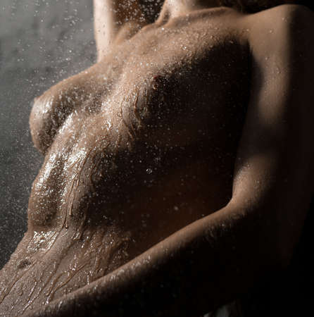 Sexy woman body under shower stream