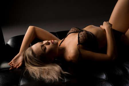 Sensual woman undress transparent black lingerie lying on sofa