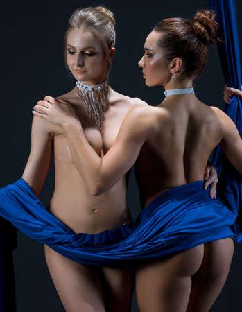 Two sexy girls posing gracefully on aerial silks 版權商用圖片
