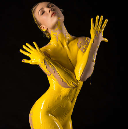 Naked woman in yellow paint in studio