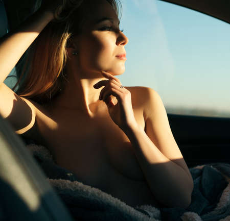 Romantic shot of a nude woman sitting in a car
