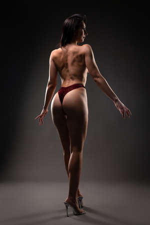 topless muscular brunette woman on high heeled shoes
