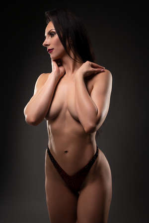 Topless woman touching neck with closed eyes