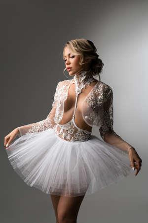 Sensual female ballet dancer touching tutu skirt