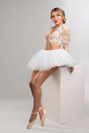 Sensual blond ballerina sitting on white block
