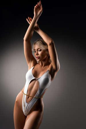 Sexy blond woman in white swimwear posing