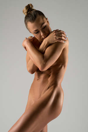Nude athletic woman standing on gray background
