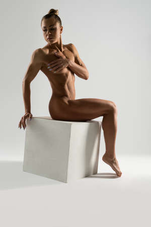 Fit naked woman sitting on white cube in studio