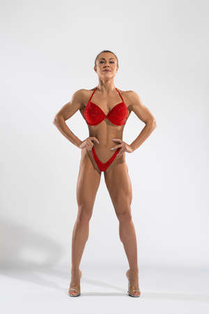 Content female bodybuilder in bikini standing in studio
