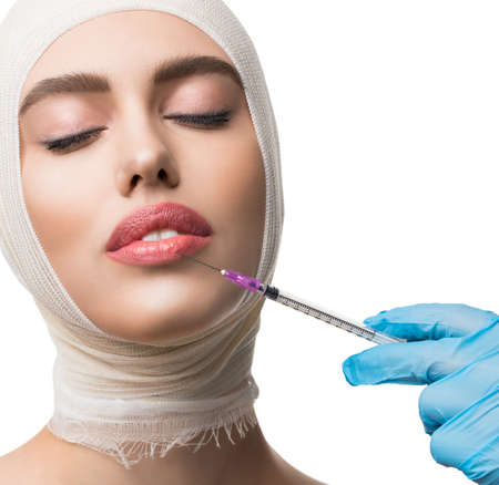 Woman her head bandaged getting lips injections