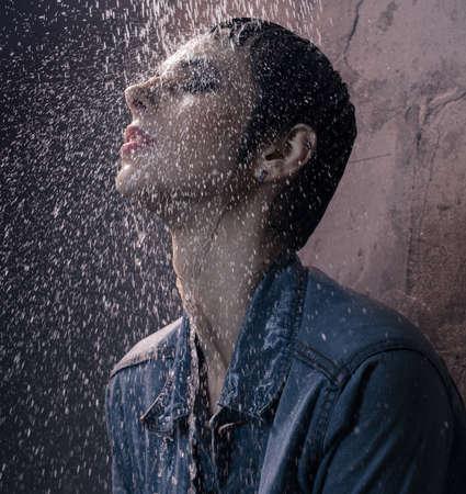 Brunette in jeanswear water falling on her face 版權商用圖片