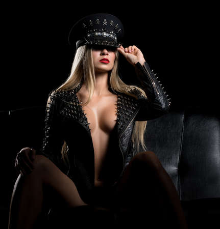 Sexy blonde topless in bdsm cap and leather jacket Stockfoto