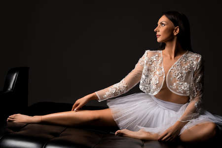 Sexy graceful woman in tutu skirt in dark studio
