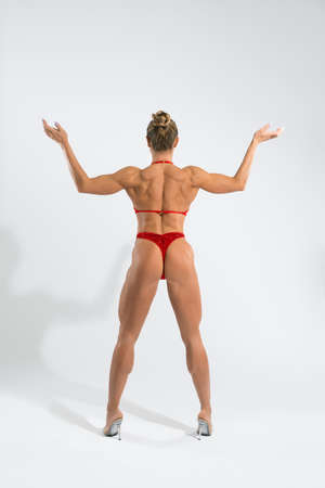 Fit female athlete show spine in red tango on white background Stockfoto