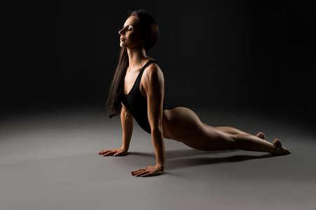 Graceful woman in bodysuit in dark studio
