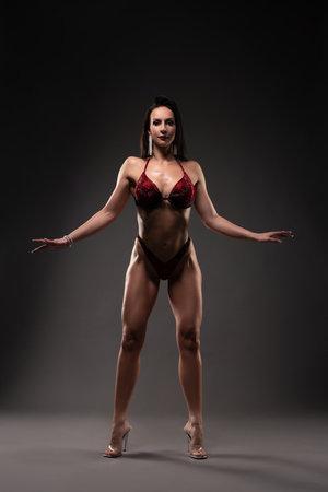 Muscular female in bikini holding hands on waist