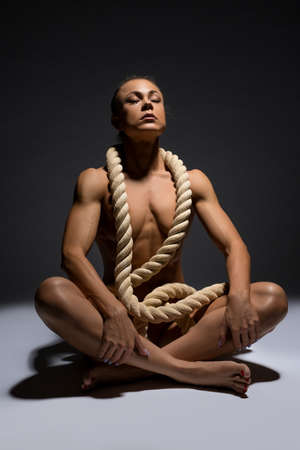 Graceful naked sportswoman with rope on breast in studio Stockfoto