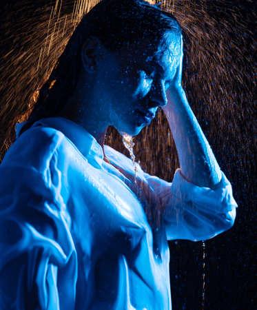 Woman in wet shirt having shower in the dark Stockfoto
