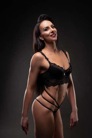 Muscular female in bikini show perfect body looking at camera