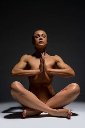 Graceful naked sportswoman with muscular body in yoga pose