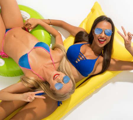 Sexy models posing on swimming mattress isolated Stockfoto