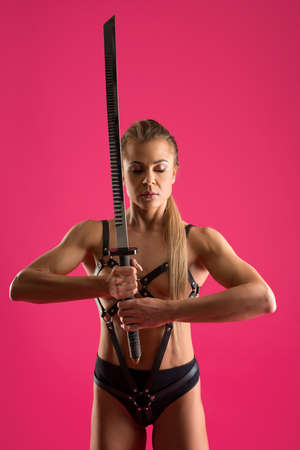 Strong woman in leather underwear with katana