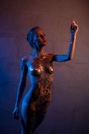 Sensual female with body art raising arm Stockfoto