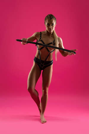 Sexy woman in erotic outfit with BDSM accessories