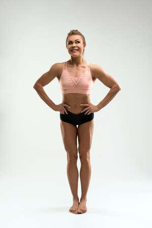 Happy fit woman in sports underwear standing in studio