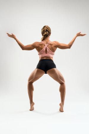 Muscular woman in sports underwear standing in Goddess pose