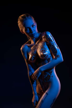 Naked woman with golden body art in darkness