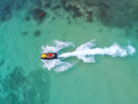 People are playing a jet ski in the sea.Aerial view. Top view.amazing nature background.The color of the water and beautifully bright. Fresh freedom. Adventure day.clear turquoise at tropical beach. Stock Photo