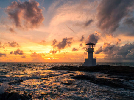 Lighthouse in the sea and evening light.
