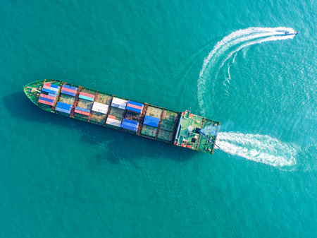 Container ship in export and import business and logistics. Shipping cargo to harbor by crane. Water transport International. Aerial view Stock Photo