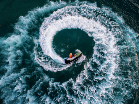 People are playing a jet ski in the sea.Aerial view. Top view.amazing nature background.The color of the water and beautifully bright. Fresh freedom. Adventure day.clear turquoise at tropical beach. Banque d'images