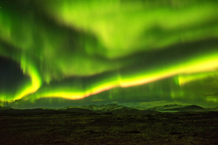 A wonderful night with Kp 5 . Northern lights mountain in Iceland. Background blurred.