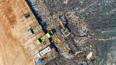A lot of waste is disposed of in the waste disposal pits. Makro is working on a mountain garbage. Aerial view and top view.