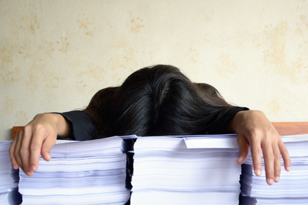 white collar worker or businesswoman tired and sleep at a table with a pile of papers Standard-Bild
