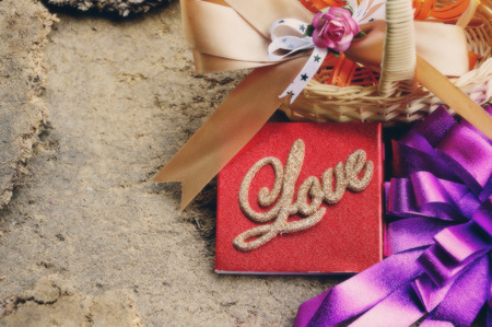 word love valentines card with ribbon, flower and basket on old wooden  valentines day background photo