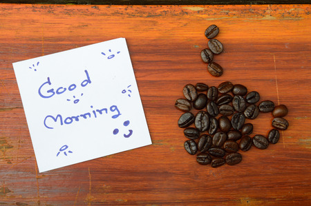 coffee beans and good morning note on the wooden background photo