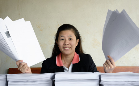 businesswoman frustrated and raise up papers into the air at a table with pile of papers photo