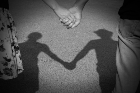 shadow of lover couple holding hand reflected on a pavement in the sunset light photo